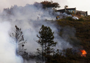 Firefighters defend a home as a wild land fire burns in the Pfeiffer Ridge area in Big Sur, Calif. on Monday De.c 16, 2013. (AP Photo/ Monterey County Herald, David Royal)