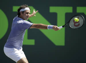 Photo - Roger Federer, of Switzerland, returns the ball to Ivo Karlovic, of Croatia, at the Sony Open tennis tournament, Friday, March 21, 2014, in Key Biscayne, Fla. Federer defeated Karlovic 6-4, 7-6 (7-4). (AP Photo/Lynne Sladky)