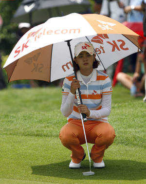 Photo -   Na Yeon Choi of South Korea uses an umbrella to shield herself from the sun as she lines up her putt on the 9th green during the first round of the LPGA Malaysia golf tournament at Kuala Lumpur Golf and Country Club in Kuala Lumpur, Malaysia, Thursday, Oct. 11, 2012. (AP Photo/Lai Seng Sin)