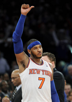 Photo - New York Knicks' Carmelo Anthony reacts to the fans after scoring 62 points and coming out of an NBA basketball game during the fourth quarter against the Charlotte Bobcats Friday, Jan. 24, 2014, at Madison Square Garden in New York. The Knicks won 125-96. (AP Photo/Bill Kostroun)