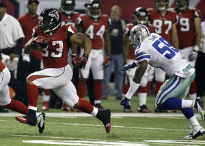 Photo -   Atlanta Falcons running back Michael Turner (33) runs away from Dallas Cowboys linebacker Ernie Sims (59) during the second half of an NFL football game, Sunday, Nov. 4, 2012, in Atlanta. (AP Photo/Chuck Burton)