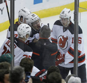 Photo - New Jersey Devils defenseman Jon Merrill (34) is helped up from the ice after he was tripped by Minnesota Wild center Torrey Mitchell during the first period of an NHL hockey game in St. Paul, Minn., Sunday, Nov. 3, 2013. Merrill left the game. (AP Photo/Ann Heisenfelt)