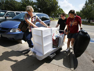 Photo - Lois Carani, left, from Ellicott City, Maryland moves daughter Emily Wong, right into the honors dorm at the University of Oklahoma with the help of Jackie Robertson on Wednesday. Photo by Steve Sisney, The Oklahoman <strong>STEVE SISNEY - THE OKLAHOMAN</strong>