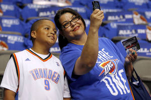 Photo - Ninnette Delaune of Anadarko, Okla., takes a picture with her great-nephew Sir'Darius Smith, 10, before Game 4 of the first round in the NBA playoffs between the Oklahoma City Thunder and the Dallas Mavericks at American Airlines Center in Dallas, Saturday, May 5, 2012. Photo by Bryan Terry, The Oklahoman
