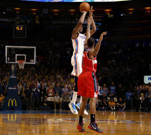 Photo - Oklahoma City's Kevin Durant (35) shoots the tying three-point shot over Washington's Trevor Ariza (1) in regulation during the NBA game between the Oklahoma City Thunder and the Washington Wizards at the Chesapeake Energy Arena, Sunday, Nov. 10, 2013. Photo by Sarah Phipps, The Oklahoman