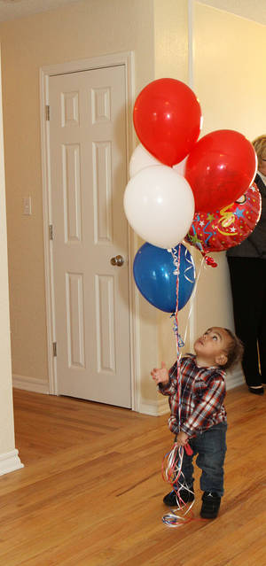 Photo - Trenton Beyard plays with balloons at a ceremony the day his family accepted a house from the Military Warriors Support Foundation and Bank of America. <strong> - PROVIDED</strong>