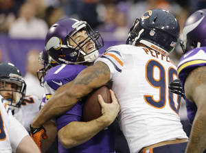 Photo - Minnesota Vikings quarterback Christian Ponder, left, is sacked by Chicago Bears defensive end Julius Peppers during the first half of an NFL football game Sunday, Dec. 1, 2013, in Minneapolis. (AP Photo/Ann Heisenfelt)