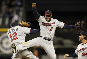 Photo -   Minnesota Twins Denard Span (2) and Alexi Casilla (12) celebrate after the team beat the Seattle Mariners in a baseball game Friday, May 4, 2012, in Seattle. The Twins won 3-2. (AP Photo/Elaine Thompson)
