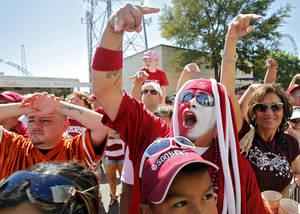 Photo - Simon Torres cheers as the Sooners' team bus arrives for the Red River Rivalry college football game between the University of Oklahoma Sooners (OU) and the University of Texas Longhorns (UT) at the Cotton Bowl on Saturday, Oct. 2, 2010, in Dallas, Texas.   Photo by Chris Landsberger, The Oklahoman