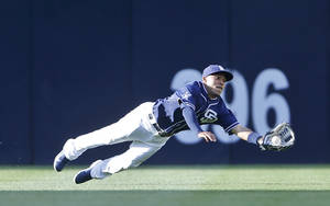 Photo - San Diego Padres center fielder Alexi Amarista makes a diving catch to rob San Francisco Giants' Hunter Pence in the first inning of a baseball game Saturday, April 19, 2014, in San Diego.  (AP Photo/Lenny Ignelzi)