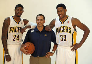 Photo - Indiana Pacers' Paul George, left, and Danny Granger, right, poses with head coach Frank Vogel during NBA basketball media day Friday, Sept. 27, 2013, in Indianapolis. (AP Photo/Darron Cummings)