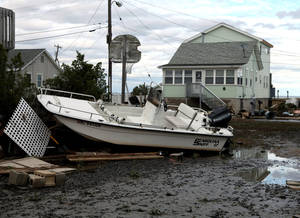 photo -   A boat tossed into a neighborhood in the wake of superstorm Sandy on Wednesday, Oct. 31, 2012, in Cedar Bonnet Island, N.J. Power is still out and residents who evacuated the island are still not being allowed back in. Sandy is considered responsible for at least six deaths across the state of New Jersey in addition to power outages. (AP Photo/Robert Ray)