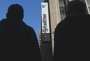 Photo - In this Monday, Nov. 4, 2013, photo, pedestrians cross the street in front of Twitter headquarters in San Francisco. As it nears its IPO, bulls and bears on Twitter appear divided less by their analysis of the company and more on their attitudes toward investing.  (AP Photo/Jeff Chiu)