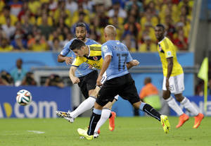 Photo - FILE - In this June 28, 2014 file photo, Colombia's James Rodriguez shoots to score his team's first goal during the World Cup round of 16 soccer match between Colombia and Uruguay at the Maracana Stadium in Rio de Janeiro, Brazil. James Rodriguez' volleyed goal for Colombia against Uruguay, controlling the ball with his chest, letting it drop and then hammering in with his left foot, all while turning to face goal, was poetry, the timing exquisite. It will be many fans' goal of the tournament. (AP Photo/Antonio Calanni, File)