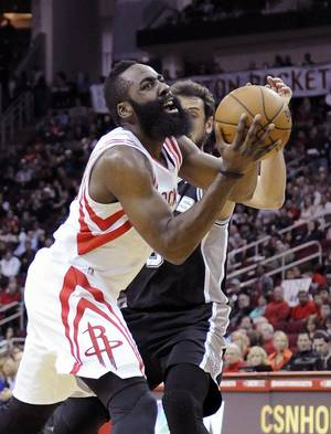 Photo - Houston Rockets' James Harden, left, pushes past San Antonio Spurs' Marco Belinelli in the first half of an NBA basketball game Monday, April 14, 2014, in Houston. (AP Photo/Pat Sullivan)