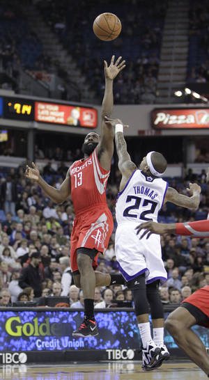 Photo - Houston Rockets guard James Harden, left, shoots over Sacramento Kings guard Isaiah Thomas during the first quarter of an NBA basketball game in Sacramento, Calif., Tuesday Feb. 25, 2014.(AP Photo/Rich Pedroncelli)