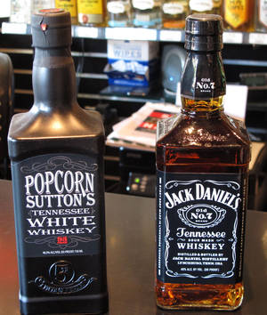 Photo - Bottles of Popcorn Sutton's Tennessee White Whiskey and Jack Daniel's Tennessee whiskey sit side by side at a Louisville, Ky., liquor store. The owner of the Jack Daniel's trademark has filed a federal lawsuit claiming the shape of the Popcorn Sutton bottle amounts to a trademark infringement because it so closely resembles the Jack Daniel's bottle. AP Photo/Bruce Schreiner.