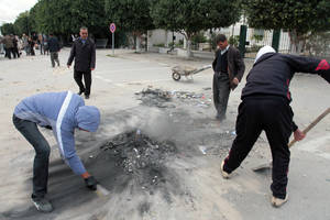 Photo - Local people clean damages in the street a day after clashes between protestors and riot police in Siliana, Tunisia, Sunday, Dec. 2, 2012. The Regional Workers Union in Siliana announced a provisional halt to the strike Sunday, hours after agreeing to a deal with the central government in Tunis, the capital of this North African nation.  (AP Photo / Amine Landoulsi)