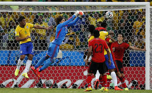 Photo - Brazil's Paulinho (8) watches as Mexico's goalkeeper Guillermo Ochoa punches the ball clear of the goal during the group A World Cup soccer match between Brazil and Mexico at the Arena Castelao in Fortaleza, Brazil, Tuesday, June 17, 2014.  (AP Photo/Eduardo Verdugo)
