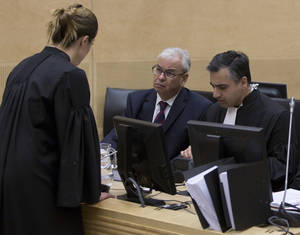 Photo -   Representatives of Libya, Ahmad Sadeq Al Gehani, center, and Payam Akhavan, right, speak to an International Criminal Court staff member before a public hearing on Libya's challenge to the admissibility of the case against Seif Al-Islam Gaddafi in The Hague, Netherlands, Tuesday Oct. 9 2012. The International Criminal Court is holding a two-day hearing into where the eldest son of former Libyan dictator Moammar Gadhafi should be put on trial. Seif al-Islam Gadhafi is charged by the international court with crimes against humanity for his alleged involvement in the deadly crackdown on dissent against his father's rule. However Libyan authorities say they want to prosecute him at home, where he is being held. (AP Photo/Michael Kooren, POOL)
