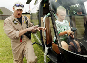 Photo - Helicopter pilot Drew Hamilton with the Oklahoma Highway Patrol explains the use of the helicopter to parents while Gabriel Inman, 8, sits at the controls.