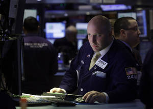 Photo - In this Thursday, Feb. 14, 2013 photo, specialist Joe Parisi works at his post on the floor of the New York Stock Exchange, in New York. Disappointing news about Germany's economy sent Asian stock markets down on Friday, Feb. 15, 2013. (AP Photo/Richard Drew)
