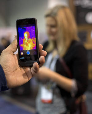 Photo - The FLIR ONE thermal imager for the iPhone is demonstrated at the International Consumer Electronics Show, Thursday, Jan. 9, 2014, in Las Vegas. The imager attaches to the back of an iPhone 5 or 5s and translates heat data into color images on the phone's screen. (AP Photo/Julie Jacobson)