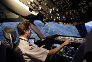 Photo -  American Airlines pilot Bill Elder, the airline's fleet training manager on the Boeing 787 Dreamliner, banks sharply to the left over the Queens and Manhattan boroughs of New York in a Boeing 787 flight simulator in Fort Worth, Texas. AP Photo  <strong>LM Otero -  AP </strong>