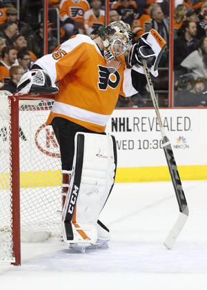Photo - Philadelphia Flyers goalie Steve Mason looks down as he leans on his stick during the first period of an NHL hockey game against the Boston Bruins, Saturday, Jan. 25, 2014, in Philadelphia.  (AP Photo/Chris Szagola)