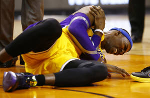 photo - L.A. Lakers Dwight Howard falls to the court and grabs his right shoulder in pain in the 4th quarter of the game against the Phoenix Suns Wednesday Jan. 30, 2013.  The Lakers, who had won three straight _ all at home, lost Dwight Howard when he reinjured his right shoulder with 6:57 to play. (AP Photo/The Arizona Republic, Rob Schumacher)