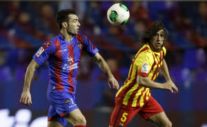 Photo - Levante's David Barral duels for the ball with Barcelona's Carles Puyol during their la Copa del Rey soccer match at the Ciutat de Valencia stadium in Valencia, Spain, Wednesday Jan. 22, 2014. (AP Photo/Alberto Saiz)