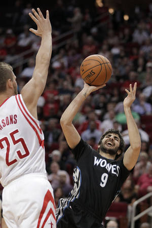 Photo - Minnesota Timberwolves guard Ricky Rubio (9) shoots as Houston Rockets forward Chandler Parsons (25) defends during the second quarter of an NBA basketball game, Thursday, March 20, 2014, in Houston. (AP Photo/Patric Schneider)