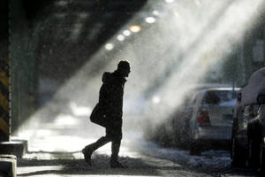 Photo - The sun illuminates windblown snow as a man walks under elevated train tracks, Wednesday, Jan. 22, 2014, in Philadelphia.  A winter storm stretched from Kentucky to New England and hit hardest along the heavily populated Interstate 95 corridor between Philadelphia and Boston.   (AP Photo/Matt Rourke)