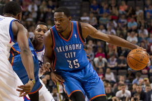 Photo - Oklahoma City Thunder's Kevin Durant, right, keeps the ball from Philadelphia 76ers' Thaddeus Young, left, as Evan Turner, centre left, looks on during their NBA preseason basketball game at the Phones4 u Arena in Manchester, England, Tuesday, Oct. 8, 2013. (AP Photo/Jon Super)