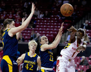 Photo - Maryland's Laurin Mincy (1) passes the ball as Drexel's Sarah Curran (5) and Meghan Creighton (22) try to block, during the first half of an NCAA college basketball game at the Comcast Center in College Park, Md., Monday, Nov. 25, 2013. (AP Photo/Jose Luis Magana)