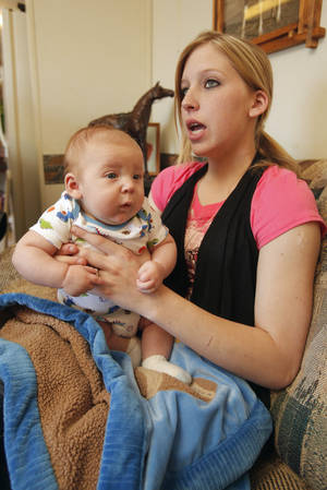 Photo - Sarah McKinley, 18, and her son Justin, 3 months old, sit on the couch of her mobile home on Wednesday in  Blanchard.  Photo by  Steve Sisney, The Oklahoman