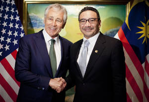 "Photo - U.S. Defense Secretary Chuck Hagel, left, meets with Malaysian Defense Minister Hishammuddin Hussein Saturday, May 31, 2014 in Singapore. Hagel warned an international security conference Saturday that the U.S. ""will not look the other way"" when nations such as China try to restrict navigation or ignore international rules and standards. (AP Photo/Pablo Martinez Monsivais, Pool)"