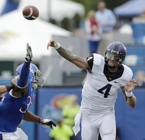Photo -   TCU quarterback Casey Pachall (4) passes under pressure from Kansas cornerback Dexter Linton (23) during the first half of an NCAA college football game, Saturday, Sept. 15, 2012, in Lawrence, Kan. (AP Photo/Charlie Riedel)