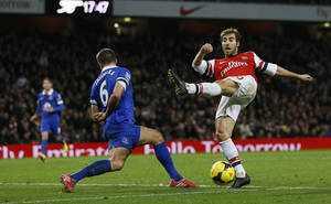 Photo - Arsenal's Mathieu Flamini, right, fails to connect with the ball as Everton's Phil Jagielka defends during the English Premier League soccer match between Arsenal and Everton at the Emirates Stadium in London, Sunday, Dec. 8, 2013. (AP Photo/Kirsty Wigglesworth)