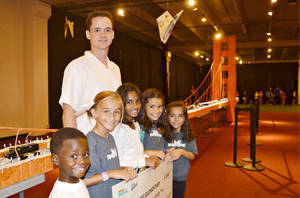 Photo - Mustang Elementary students stand in front of their replica of the Golden Gate Bridge, made from 26,000 milk cartons. Pictured, from left, are students Ashton Perry, Presley Barks, Kaitlyn Samuel, Gabby Diaz and  Ariana Diaz, with art teacher   Kent Hathaway standing behind them.  PHOTO PROVIDED <strong>PROVIDED</strong>