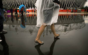 Photo -   Visitors walk during raining at the Olympic Park during the 2012 Summer Olympics, Sunday, July 29, 2012, in London. (AP Photo/Emilio Morenatti)