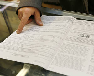 Photo - Darren Burger, co-owner of Locked and Loaded, shows the paperwork for a background check, a Form 4473 Firearms Transaction Record, at the store in Choctaw. Photo by Nate Billings, The Oklahoman