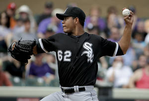 Photo - Chicago White Sox starting pitcher Jose Quintana throws against the Colorado Rockies during the third inning of a spring exhibition baseball game in Scottsdale, Ariz., Sunday, March 23, 2014. (AP Photo/Chris Carlson)