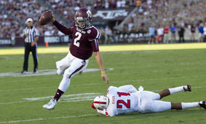 Photo - Texas A&M quarterback Johnny Manziel (2) rushes for a 7 yard touchdown as he avoids the tackle of SMU defensive back Kenneth Acker (21) during the first quarter of an NCAA college football game Saturday, Sept. 14, 2013, in College Station, Texas. (AP Photo/Bob Levey)