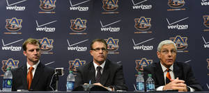 photo - Auburn NCAA college footall coach Gus Malzahn, center,  listens while his newly named defensive Ellis Johnson, right, and offensive coordinator Rhett Lashlee, left, speak during a news conference on Friday, Dec. 7, 2012 in Auburn, Ala.(AP Photo/Todd J. Van Emst)