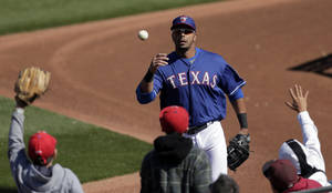 photo - Texas Rangers' Nelson Cruz tosses a foul ball to fans during an exhibition spring training baseball game against the Kansas City Royals, Sunday, Feb. 24, 2013, in Surprise, Ariz. (AP Photo/Charlie Riedel)