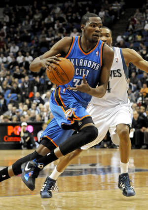 Photo - Oklahoma City Thunder's Kevin Durant, left, drives by Minnesota Timberwolves' Wesley Johnson in the second half of an NBA basketball game Wednesday, Jan. 26, 2011 in Minneapolis. The Thunder won 118-117 in overtime. Durant led the Thunder with 47 points and 18 rebounds. (AP Photo/Jim Mone)