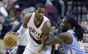 Photo - Portland Trail Blazers forward LaMarcus Aldridge, left, works the ball against Denver Nuggets forward Kenneth Faried during the first half of an NBA basketball game in Portland, Ore., Thursday, Jan. 23, 2014. (AP Photo/Don Ryan)