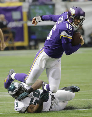 Photo - Minnesota Vikings quarterback Matt Cassel (16) tries to break a tackle by Philadelphia Eagles inside linebacker DeMeco Ryans during the first half of an NFL football game, Sunday, Dec. 15, 2013, in Minneapolis. (AP Photo/Ann Heisenfelt)