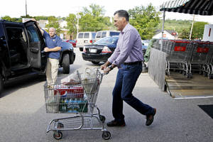 Photo -   Republican presidential candidate, former Massachusetts Gov. Mitt Romney pushes a shopping cart after buying groceries at Hunter's Shop and Save supermarket in Wolfeboro, N.H., Monday, Aug. 6, 2012. (AP Photo/Charles Dharapak)